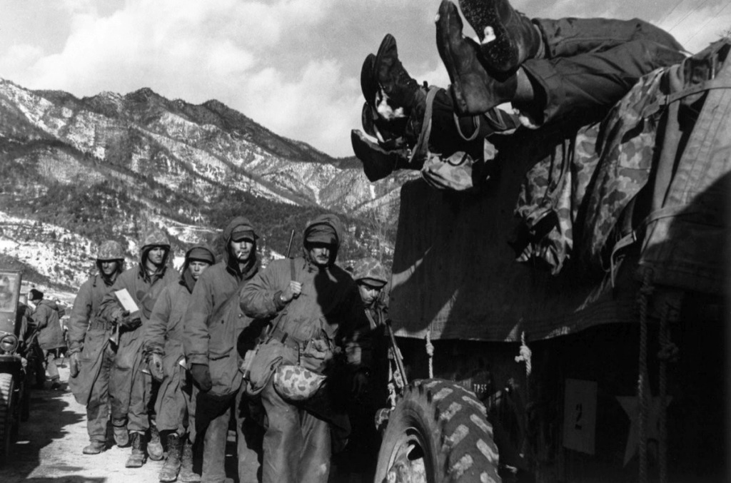 David Douglas Duncan - Marines File Past a Truck Load with Dead Troops during Retreat from Chosin Reservoir