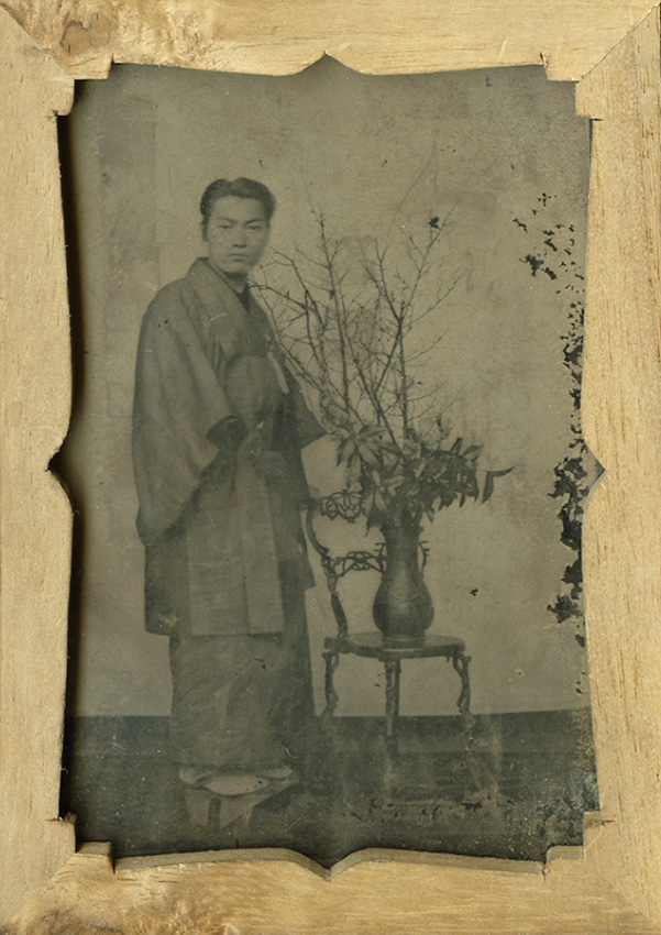 Anonymous - Portrait of a Man in Traditional Dress, Standing Next to a Flower Arrangement Posed on a Chair
