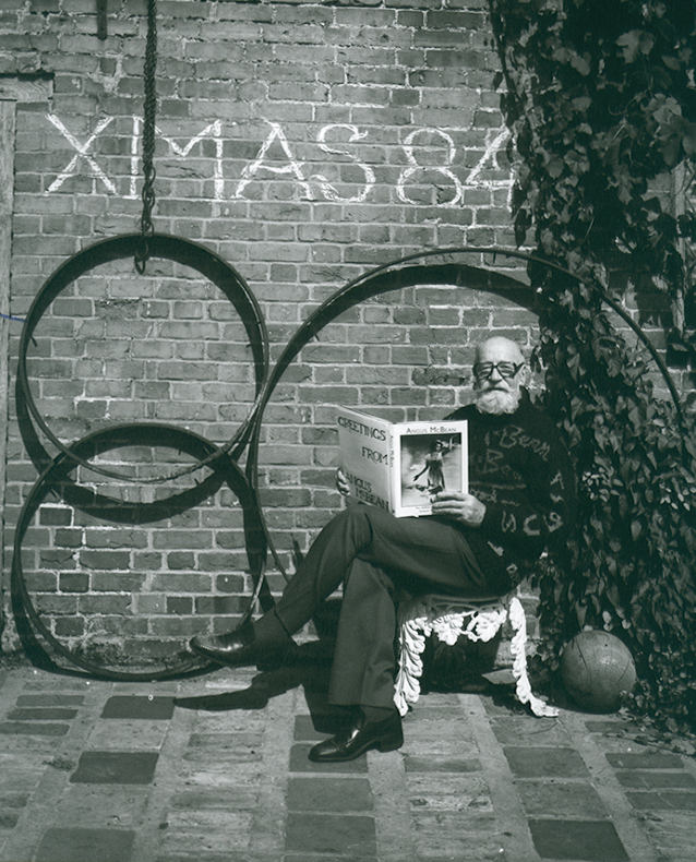 Angus McBean - Christmas Card 1984 - Self Portrait, Reading His Own Book in a Garden