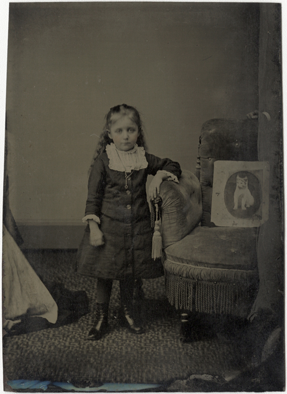 Anonymous, American - Portrait of a Sad Girl Standing Next to a Chair Holding a Picture of her Departed Cat