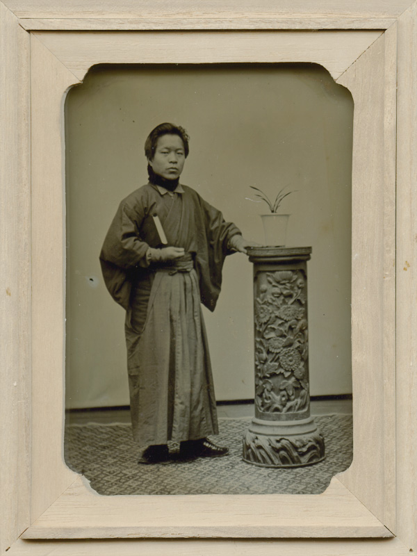 Izumi (Studio) - Young Man With Book Before Ornately Carved Pedestal